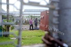 Police officers investigate the crime scene where a body was found inside the Xclent Transport Fiji yard in Lautoka yesterday. Picture: REINAL CHAND